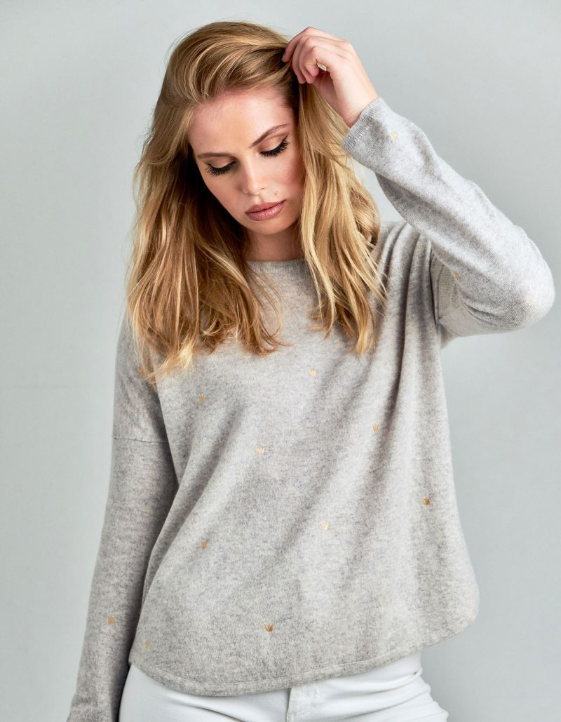 Studio picture of a model wearing a malin darlin Hundred Crowns cashmere jumper in grey marl colourway.