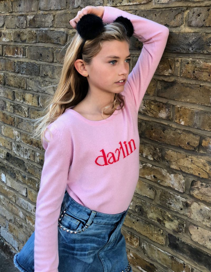 A girl leaning against a brick wall, wearing a malin darlin Little Darlin pink kids cashmere jumper.