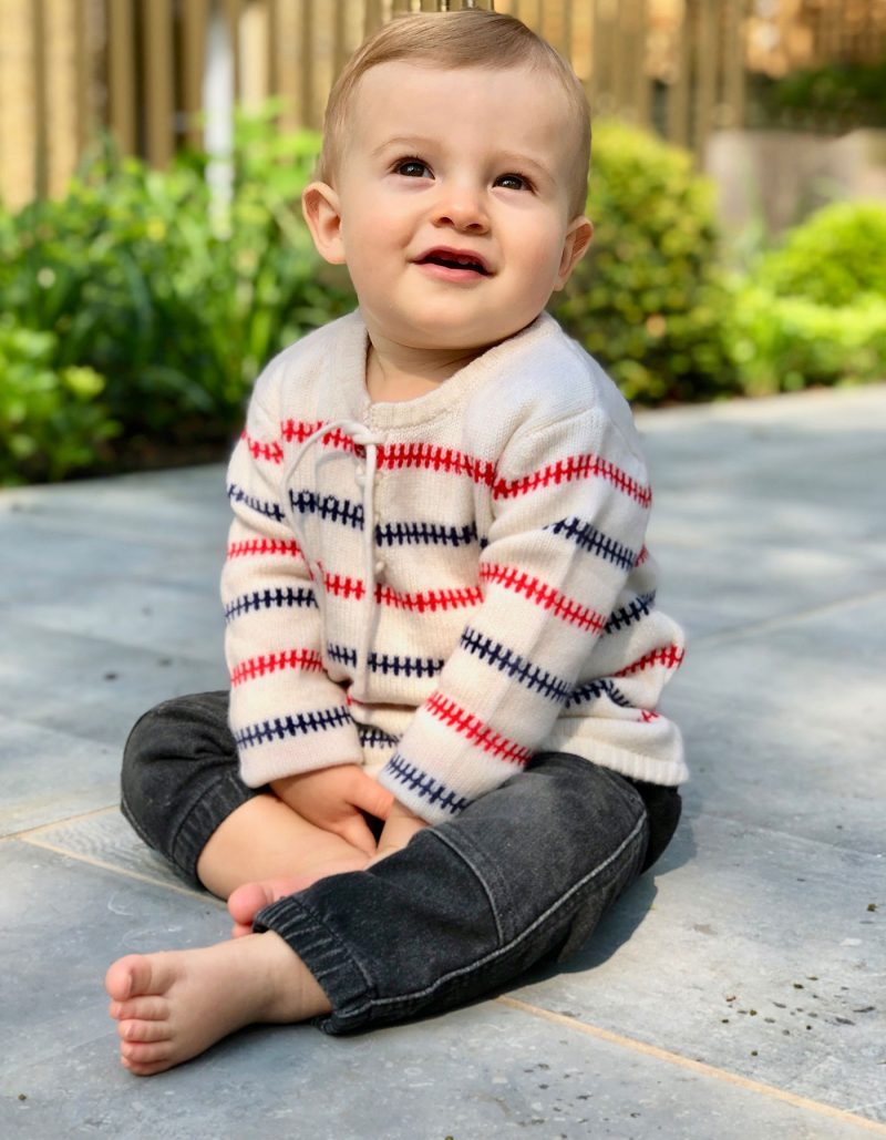 A smiling child in the Baby Fisher kids cashmere jumper, part of the malin darlin childrens cashmere collection.