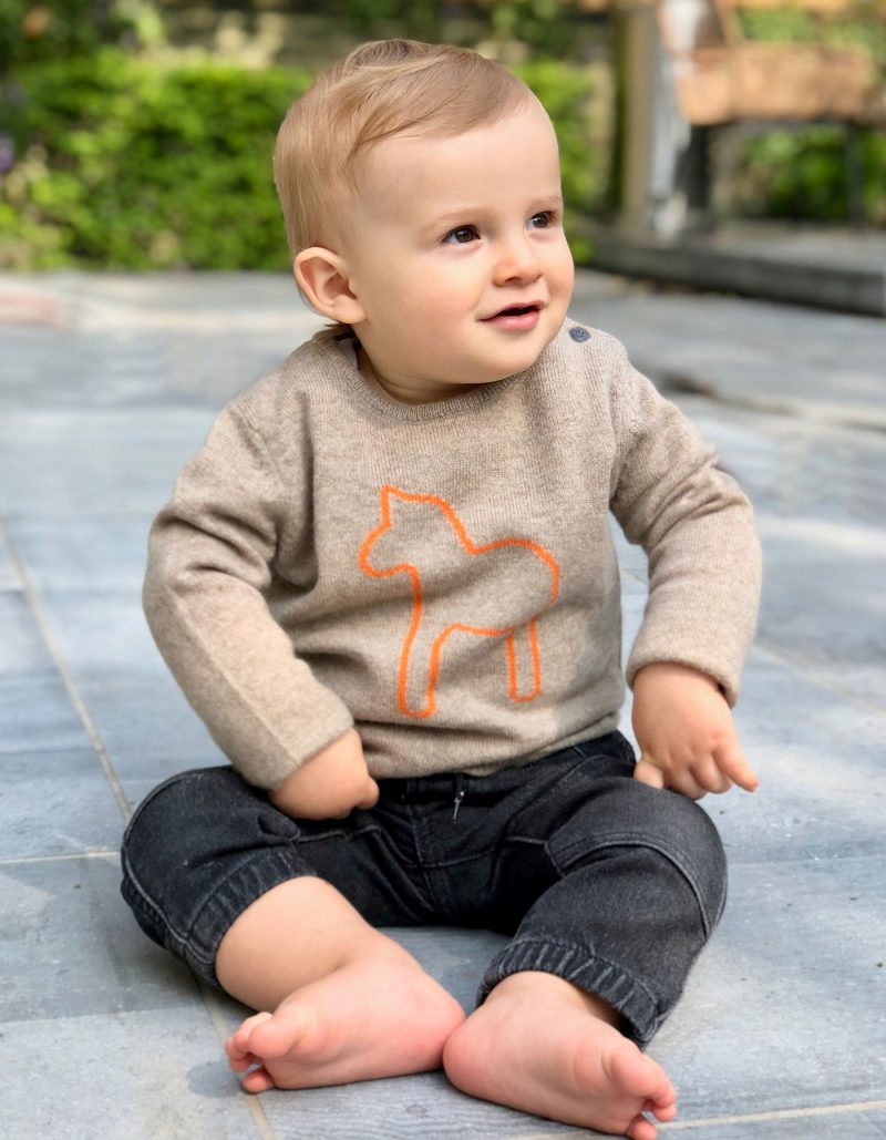 A smiling child wearing the malin darlin Baby Pony beige kids cashmere jumper with washed black jeans.