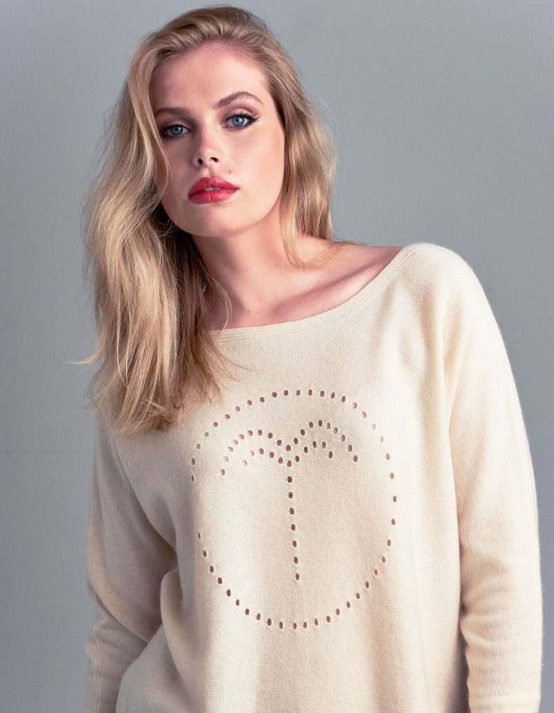 Studio photo of a model wearing a cashmere palm jumper in cream, part of the malin darlin designer cashmere collection.