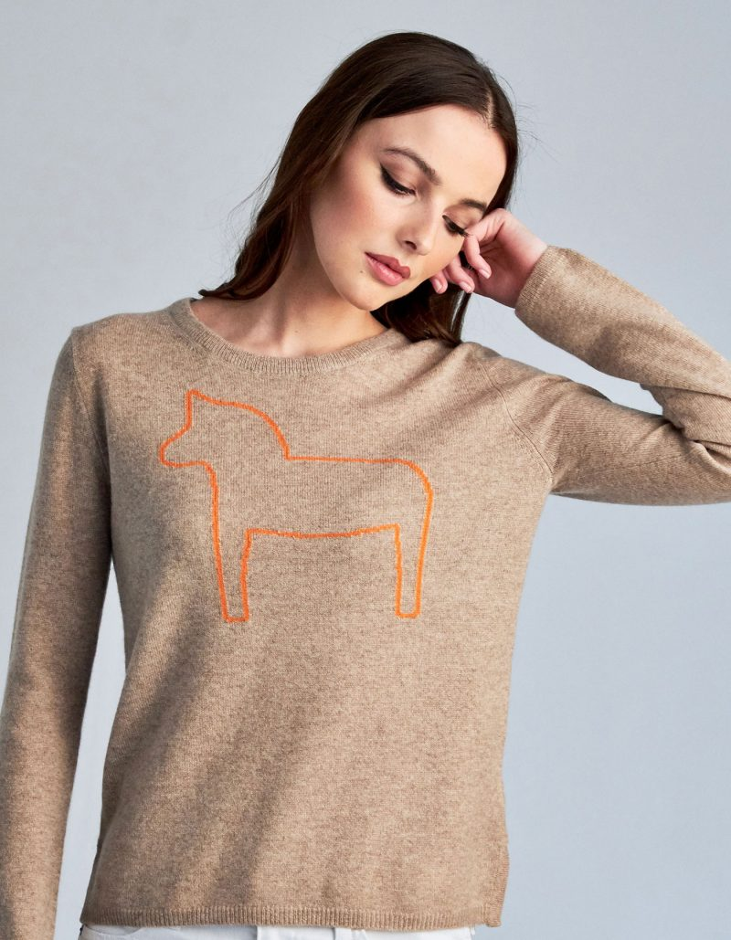 An image of a woman in one of the malin darlin Dalahast horse cashmere jumpers, a pony depicted on beige cashmere.
