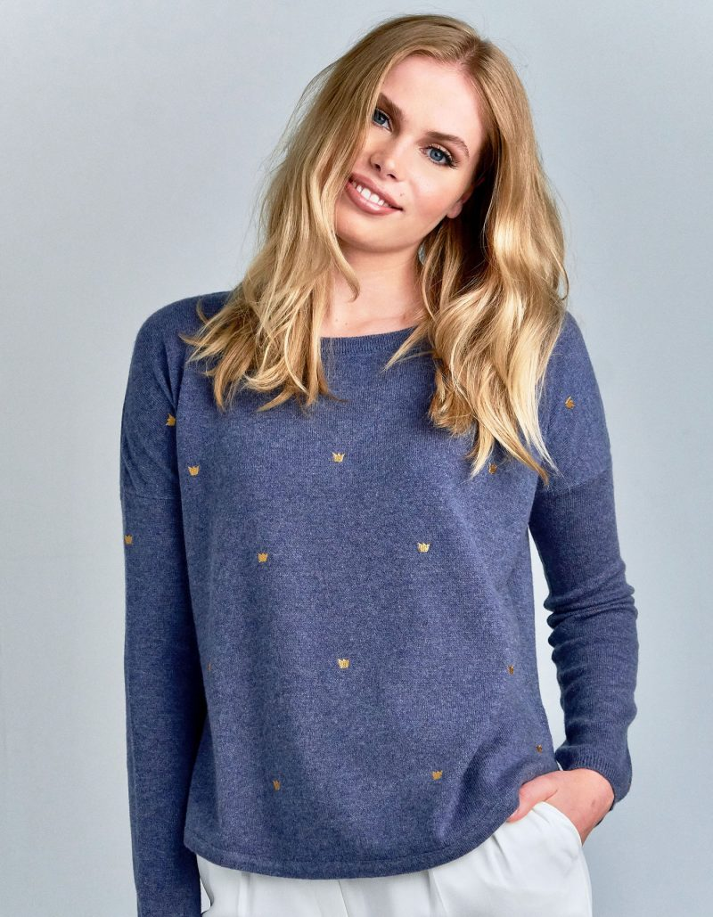 A smiling woman wearing a malin darlin Hundred Crowns blue cashmere jumper.