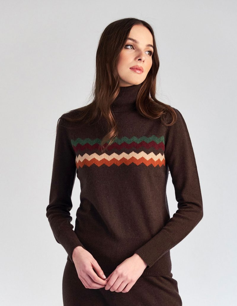 Woman wearing a designer cashmere jumper decorated with zigzag patterns.