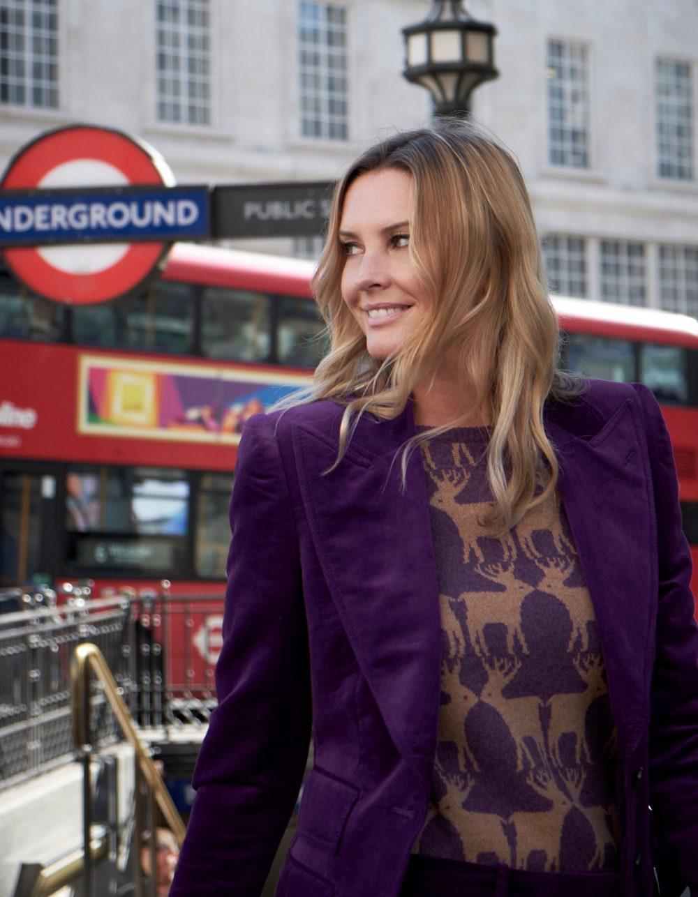 Model outside a London underground station wearing cashmere knitwear, the malin darlin Reindeer purple cashmere jumper.