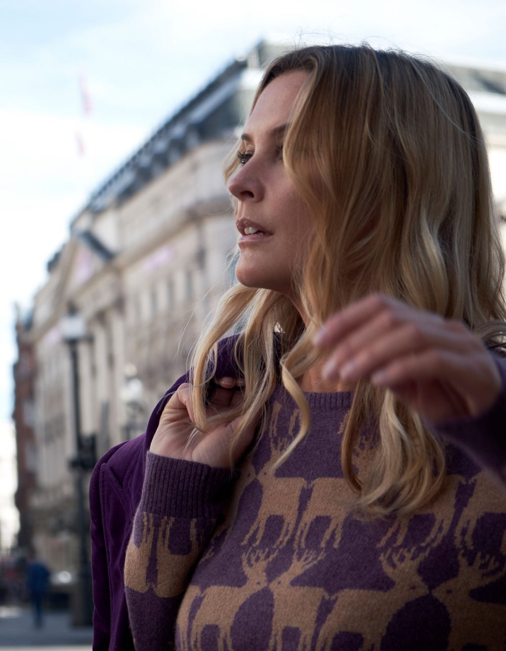 Close up of a woman in a city wearing cashmere knitwear, the malin darlin Reindeer purple cashmere jumper.