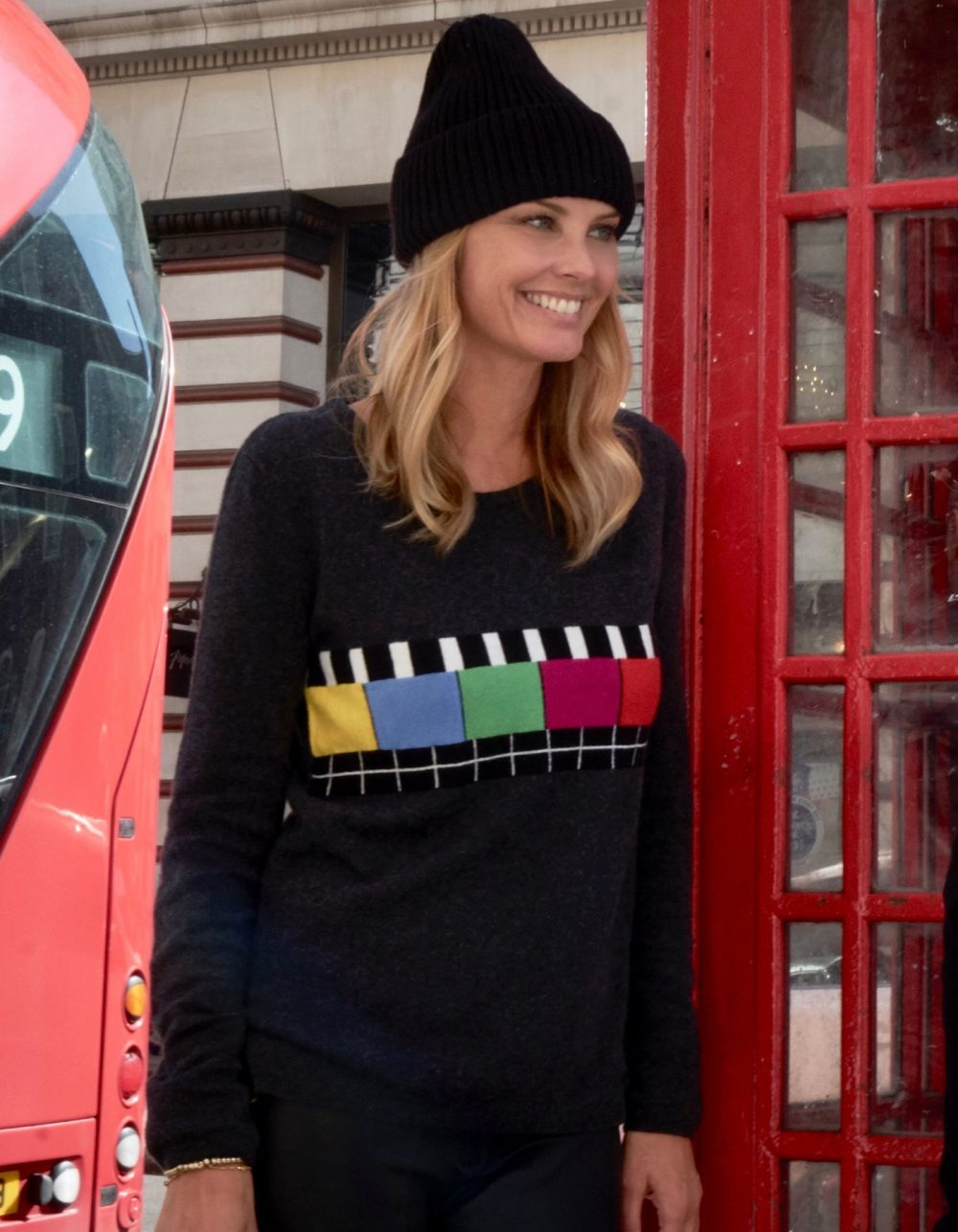 Woman by a red London telephone box wearing womens cashmere, the malin darlin Test Bild charcoal cashmere jumper.