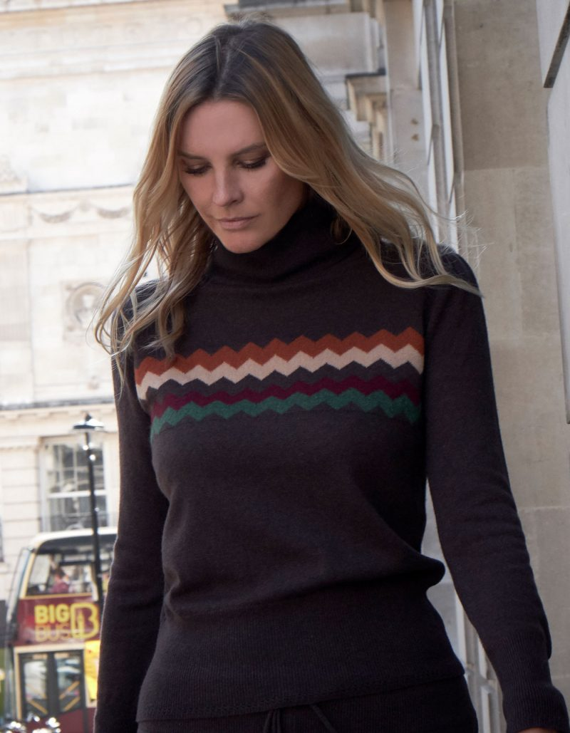 Woman on a busy street wearing malin darlin cashmere knitwear, the Zigzag chocolate cashmere jumper.
