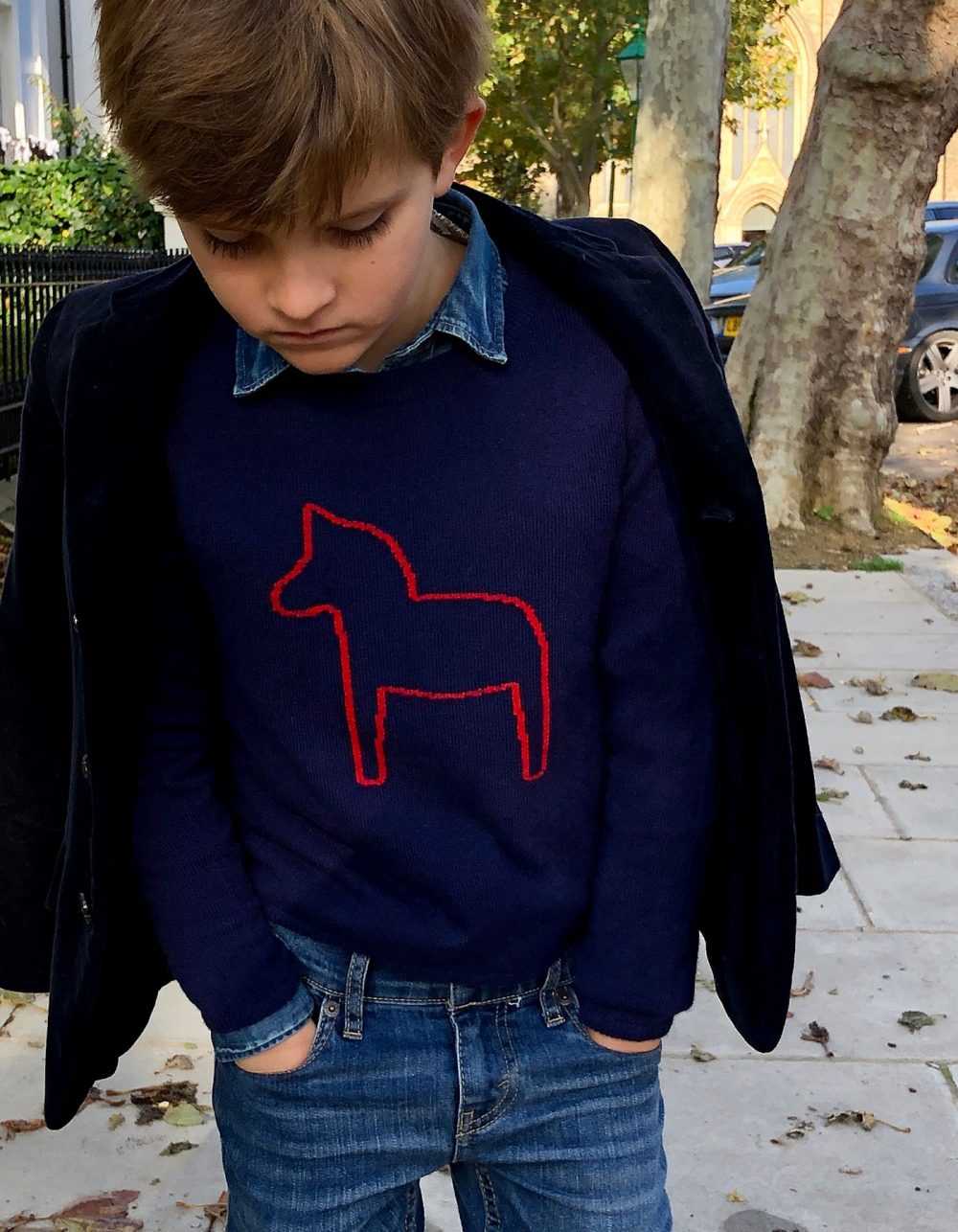 Boy wearing childrens cashmere, a malin darlin Little Pony navy cashmere jumper, under a jacket.