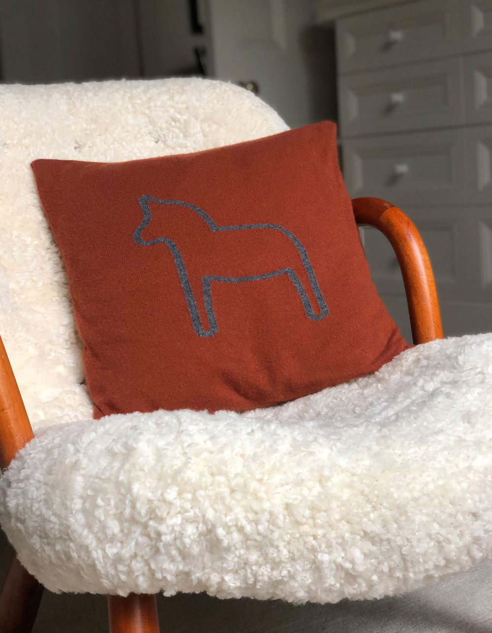Image of a rust coloured designer cashmere cushion cover, part of the malin darlin range of cashmere gifts.