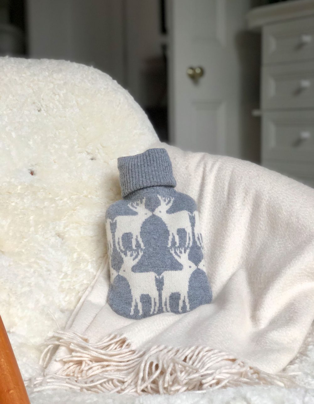 Cashmere hot water bottle on a chair, part of the malin darlin range of designer cashmere gifts.