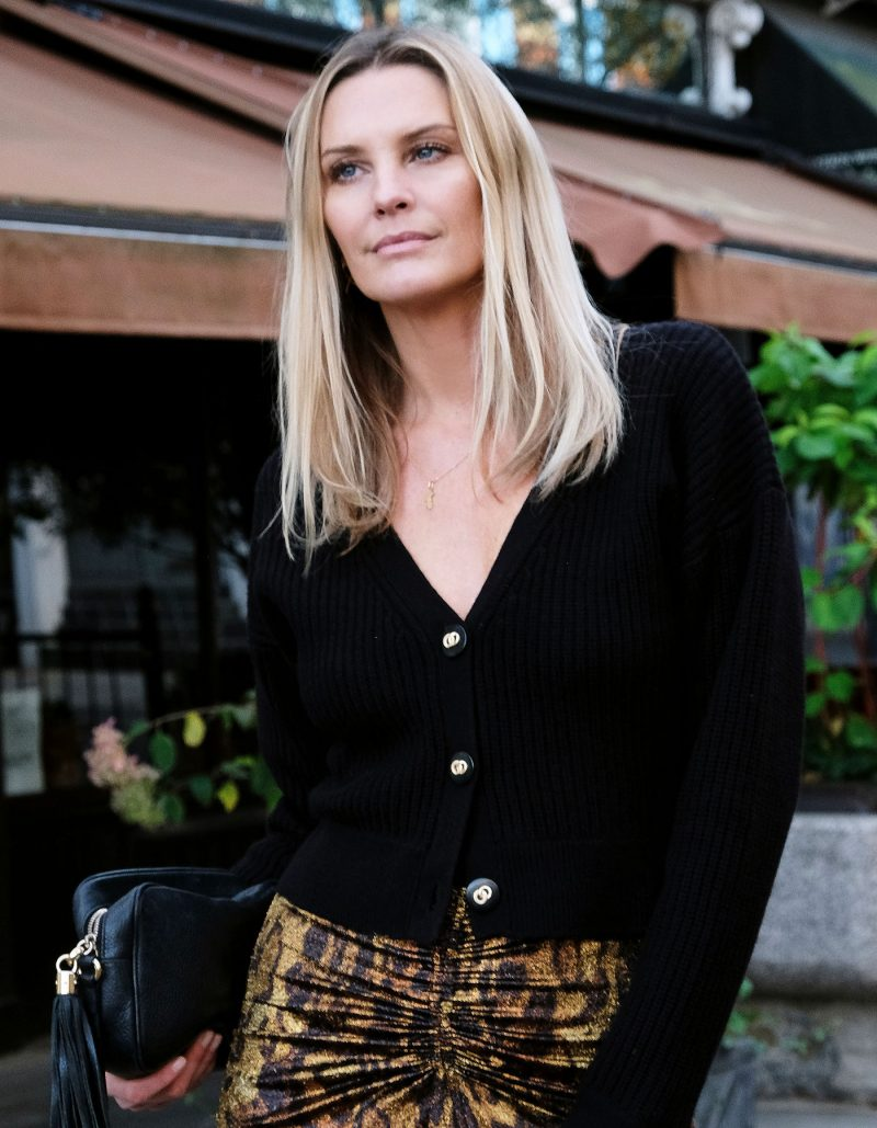 The malin darlin Coco rib cardigan, a black wool cashmere cardigan, worn by a model standing outside a restaurant.