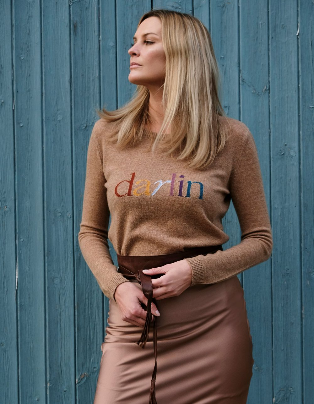 Model in the Darlin Beige cashmere jumper against a wood panel background to show sustainable womens cashmere.