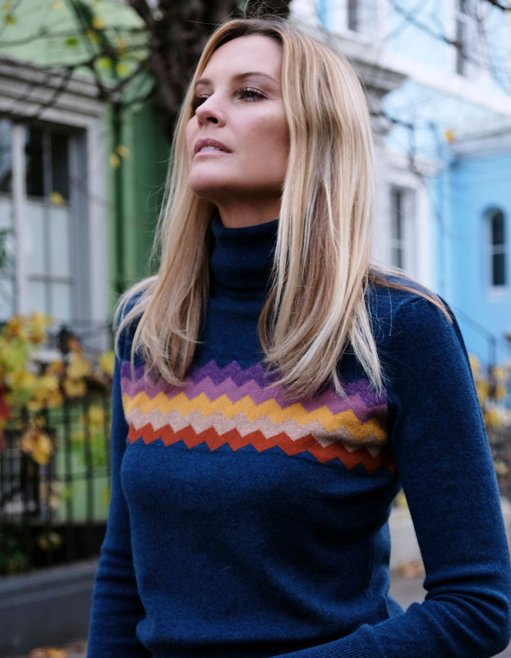 A woman wearing malin darlin cashmere knitwear, the Zigzag Blue cashmere jumper, with houses in the background.