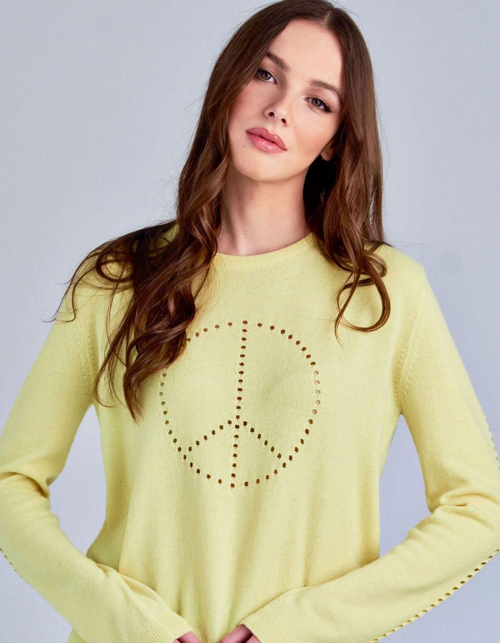 A studio shot of a model in designer cashmere knitwear, the malin darlin Peace cashmere jumper.