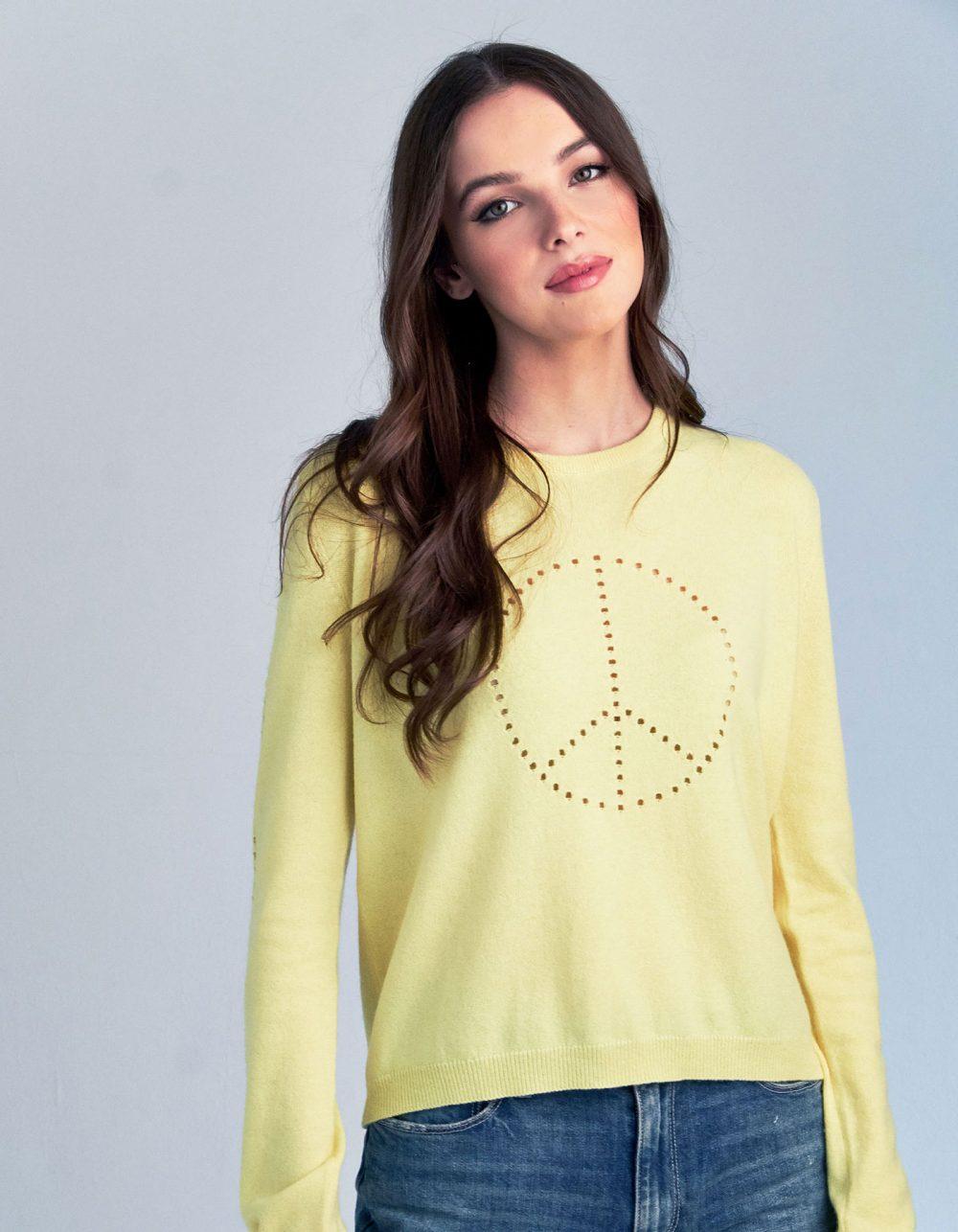 Studio photograph of a woman wearing a malin darlin Peace cashmere jumper.