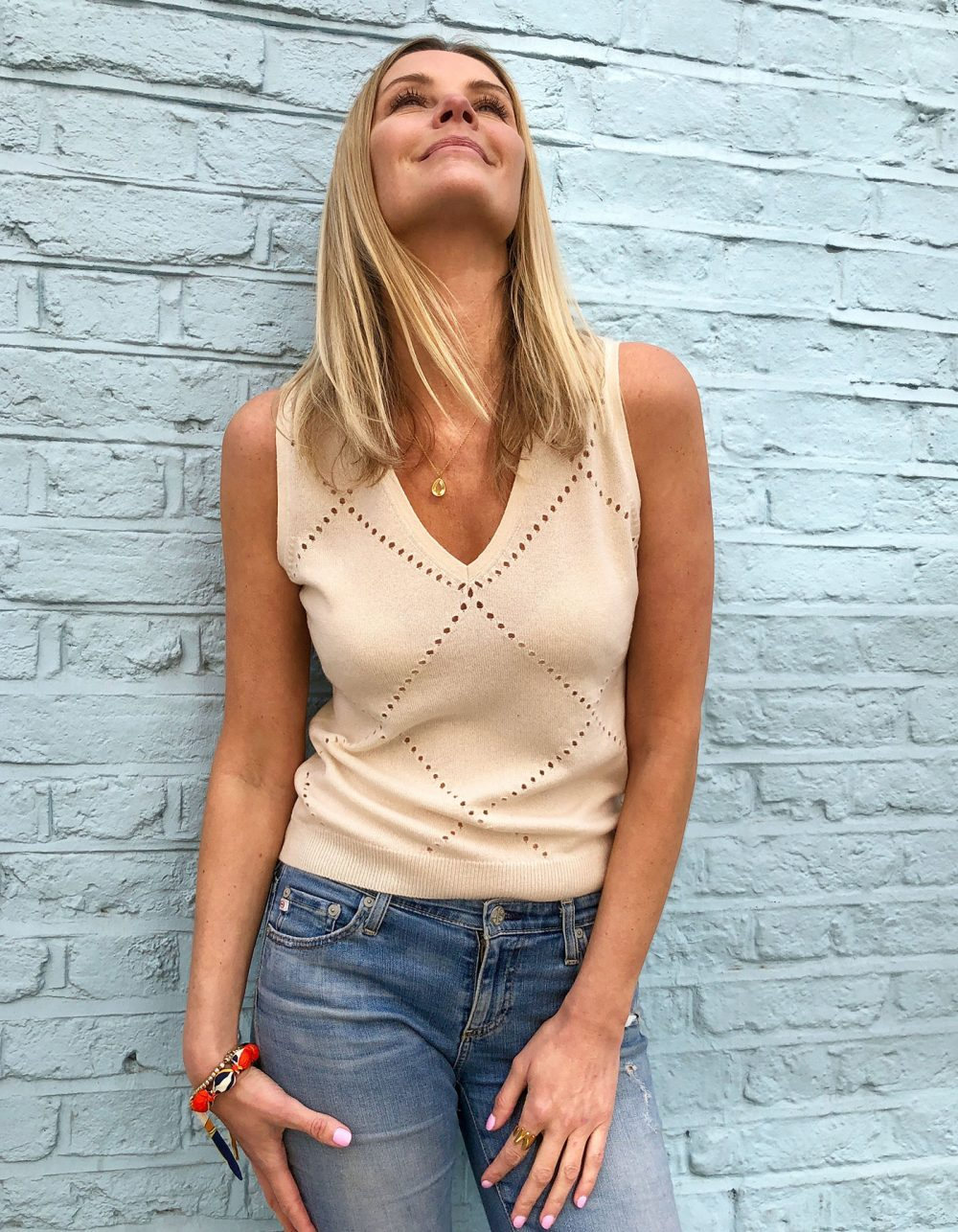 A model leaning against a brick wall wearing womens cashmere, a malin darlin Katie vest cashmere jumper.
